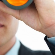 Closeup of a young business man looking through binocular