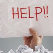 Businessman buried under crumpled pile of papers with a help sign